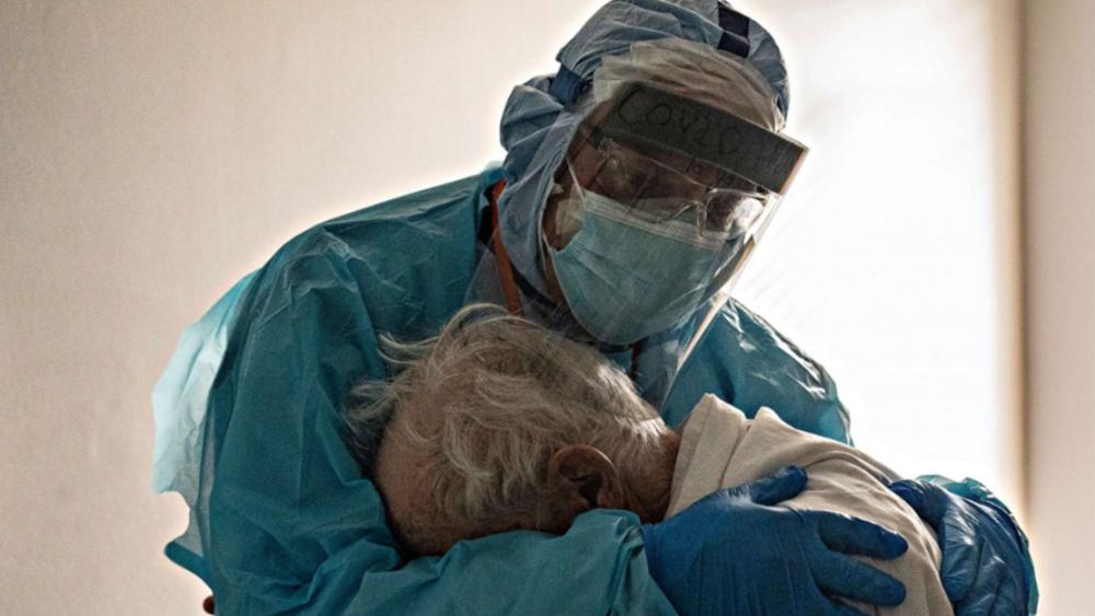 Η φωτογραφία γιατρού που αγκαλιάζει ηλικιωμένο ασθενή, σύμβολο της απελπισίας της χρονιάς του νέου κορονοϊού